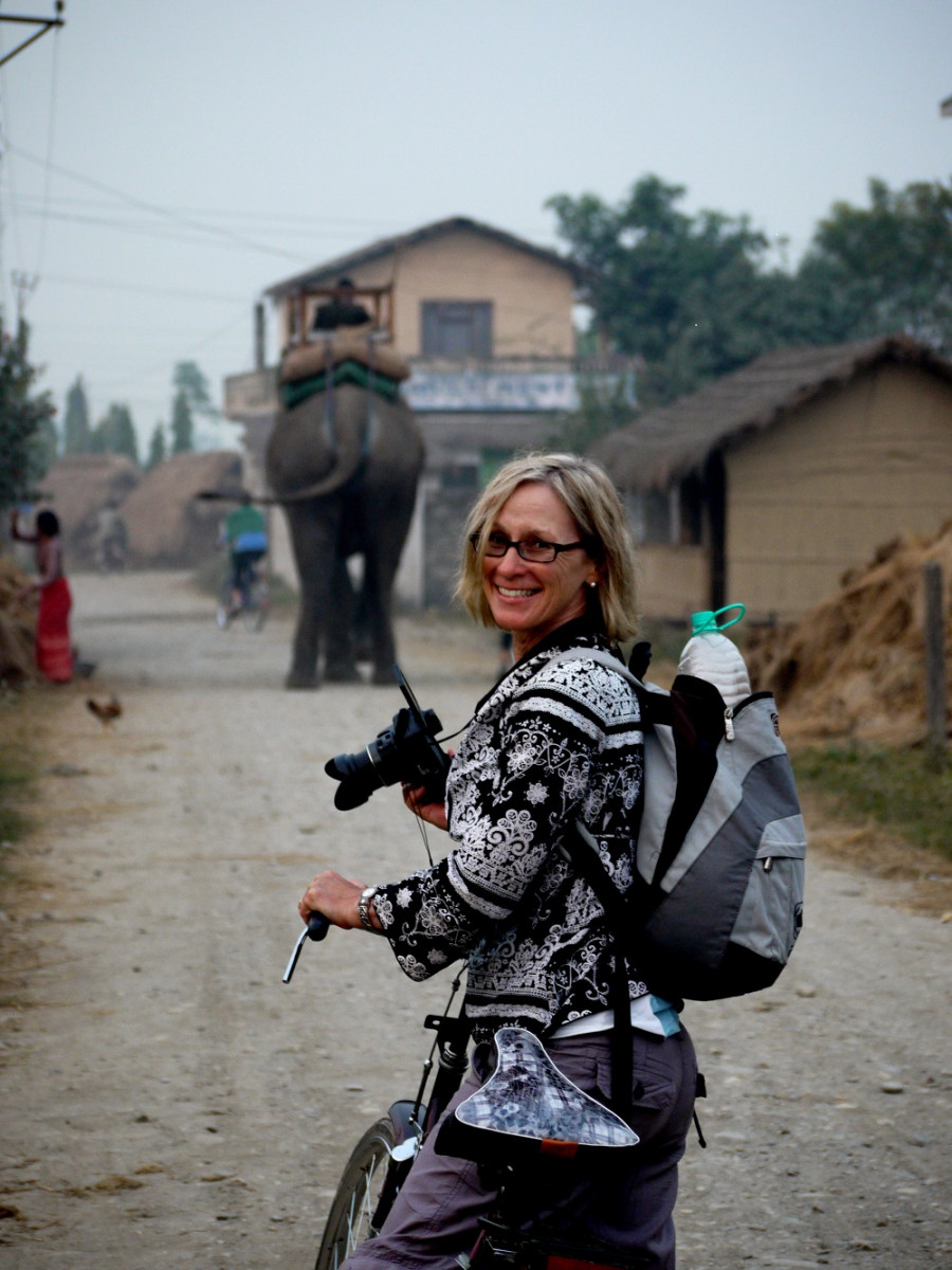 Penny on bike in Nepal with elephant